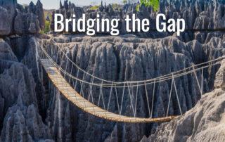 Rope bridge crossing chasm between stone cliffs